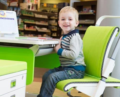 Kleiner Junge auf einem grünen Kinderstuhl von Moll