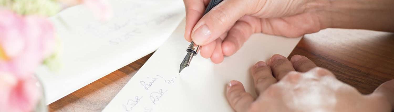 Papeterie - Hand schreibt mit Füller einen Brief