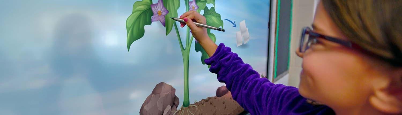Schülerin malt auf einem Promethean-ActivPanel mit einem Stift