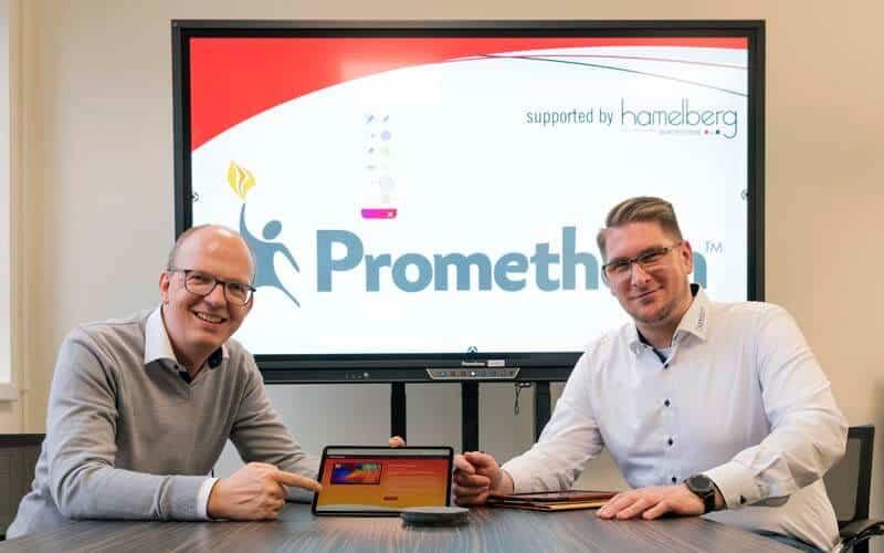 Zwei hamelberg Mitarbeiter vor digitaler Tafel